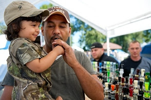 Man uses a duck call with help from toddler who he's holding