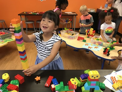 Young girl building LEGO tower