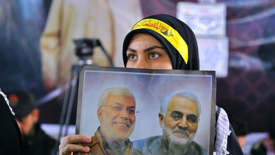A woman holds a poster showing Gen. Qasem Soleimani, right, head of Iran's Quds force.