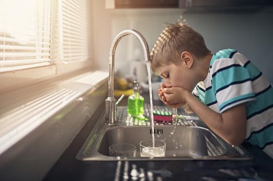 Boy drinking water from hands at kitchen sink