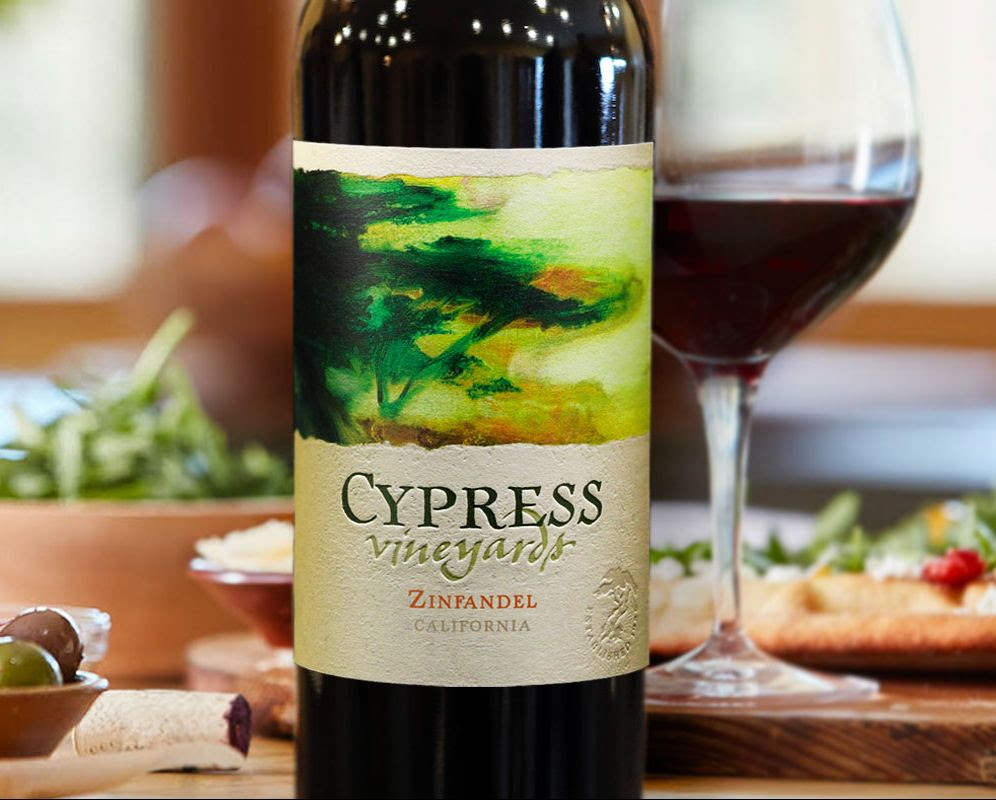 Bottle and glass of Cypress Vineyards Zinfandel on a table next to inviting food.