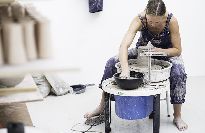 A photograph of maker Cara Guthrie at work on the wheel in her studio. She is wearing an overall covered in clay and working on an item. The studio has white walls and floors, and there are ceramics objects out of focus on the left hand side.