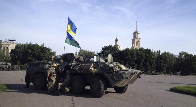 Soldados ucranianos hacen guardia en la ciudad ucraniana oriental de Slaviansk tras recapturarla e izar la bandera nacional en sus edificios oficiales.