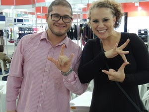 Eduardo e Ruth fazem os gestos que significam 'Festival de Dança de Joinville' em Libras