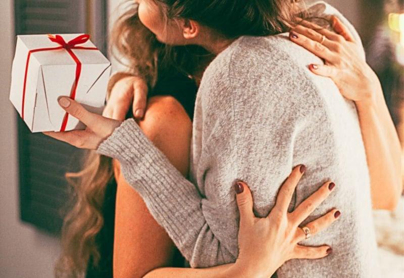 women hugging over good Christmas gift