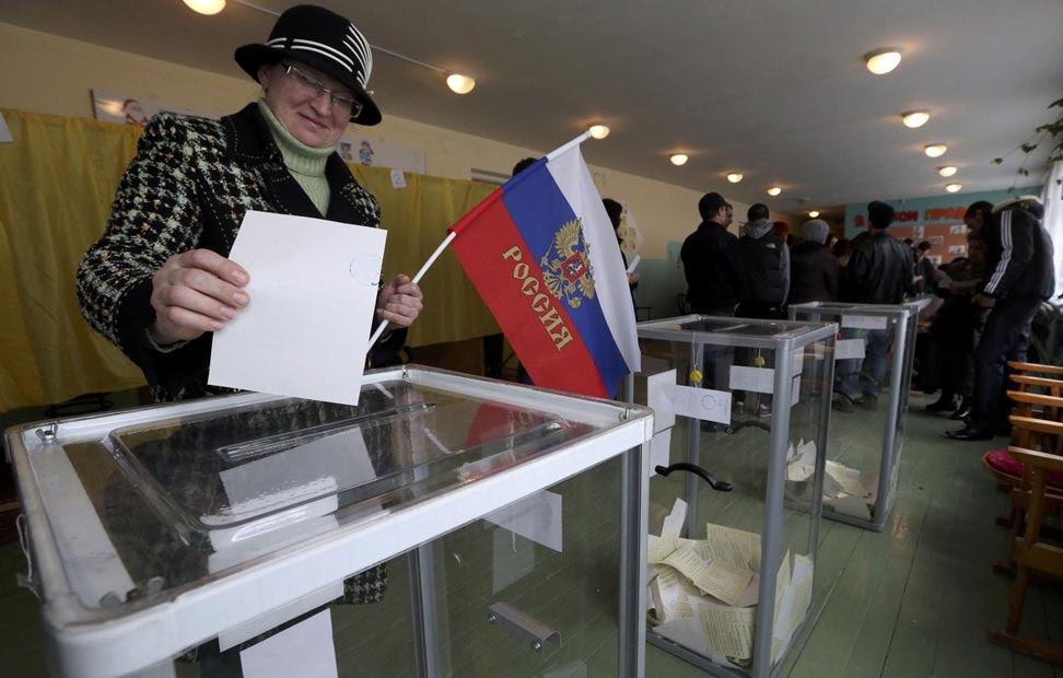 Una mujer vota mientras sostiene una bandera rusa, a estas horas más del 30% de la población ya ha ejercido su voto.