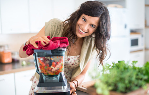 A woman using a blender to blend vegetables.