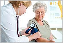 A woman getting her blood pressure taken by a nurse.