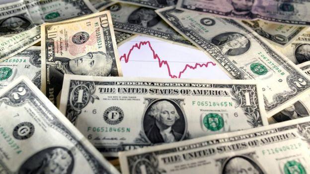 Dólares com gráfico atrás
