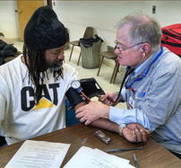 MRC volunteer takes patient's blood pressure