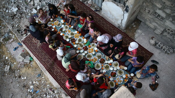 June 20, 2017: Douma — Girls break their daylight fast amid damaged buildings during a Ramadan iftar.