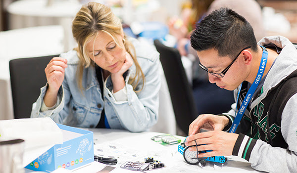 Two teachers working together building a robot