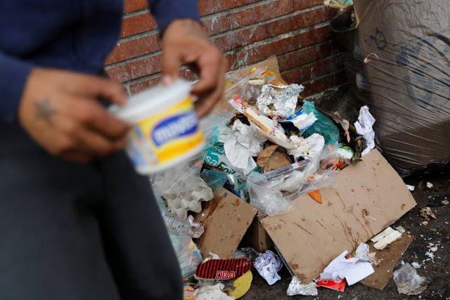 Un hombre que dijo que trabaja como guardia de seguridad, busca comida junto a un cubo de basura en Caracas. REUTERS / Carlos Jasso