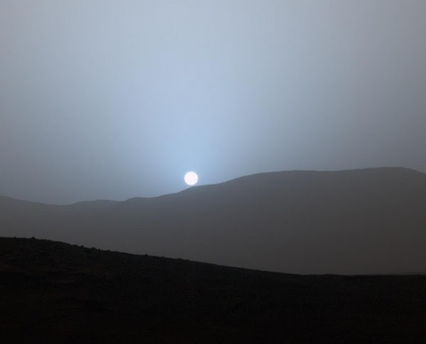 Sunset in Mars' Gale Crater. NASA's Curiosity Mars rover captured the sun setting on April 15, 2015 from the rover's location in Gale Crater. The color has been calibrated and white-balanced to remove camera artifacts. Mastcam sees color very similarly to what human eyes see, although it is actually a little less sensitive to blue than people are. Dust in the Martian atmosphere has fine particles that permit blue light to penetrate the atmosphere more efficiently than longer-wavelength colors. That causes the blue colors in the mixed light coming from the sun to stay closer to sun's part of the sky, compared to the wider scattering of yellow and red colors. Image via NASA/JPL-Caltech/MSSS
