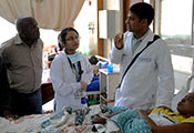 Dr. Omar Siddiqi stands next to bedside of patient, speaks with patient's family and another medical worker.