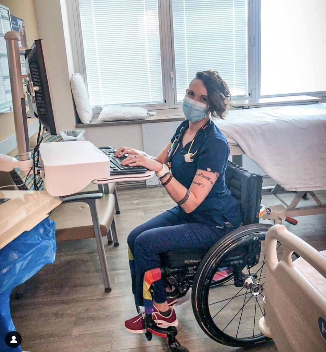 A photo of a woman in blue nurse dress and a face mask sitting in a wheelchair