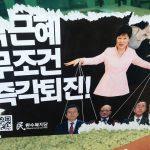 """Sur cette affiche placardée à Séoul, appelant à la destitution de la la présidente sud-coréenne présentée comme une marionnette, on peut lire : """"Park Geun-hye, démission immédiate et sans condition"""". Ce poster, copie parodique d'affiches de partis officiels, jusque dans le nom du parti inventé de toutes pièces """"Parti de la démocratie du peuple"""", est caractéristique du vent de liberté qui anime la jeunesse. Cette photo prise à Séoul date du 11 décembre 2016, deux jours après que l'Assemblée nationale a voté la destitution de la présidente le vendredi 9 décembre."""