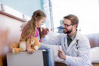 Caucasian Doctor Treating Young Caucasian Girl Holding a Teddy Bear