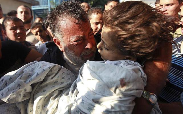 El palestino Akram Miqdad llora mientras saca en brazos el cadáver de su hija Bara-a, de seis años, de la morgue del hospital de Shifa en Gaza capital, hoy, martes 28 de julio de 2014.
