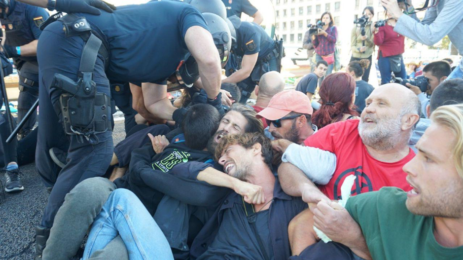 Rebels sat on the floor, linking their arms and bodies as police officers dressed in riot gear attempt to pull them away from the ground.