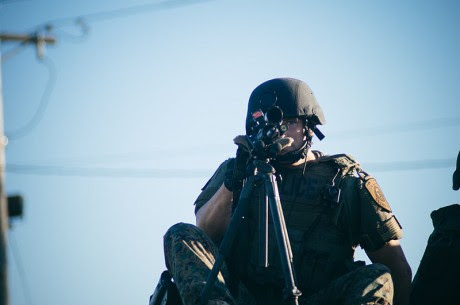 Police sharpshooter with weapon trained in the direction of the camera at protests in Ferguson - Photo by Jamelle Bouie