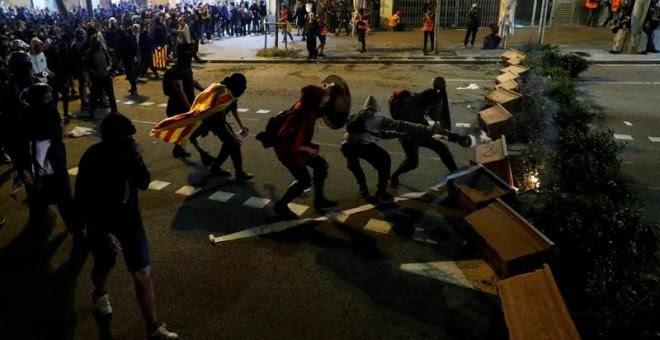 Varios manifestantes montan una barricada en el centro de Barcelona, (REUTERS)