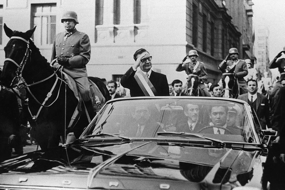 El presidente de Chile, Salvador Allende, saluda a sus seguidores desde su coche descubierto, en Santiago, pocas semanas después de su elección. A su lado, a caballo, es escoltado por el general Augusto Pinochet. AFP