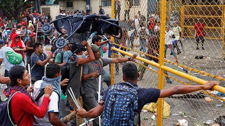 Los migrantes centroamericanos empujan la puerta de la frontera mientras intentan internarse en México y seguir con rumbo a EE.UU., en Tecún Uman (Guatemala), 28 de octubre de 2018.