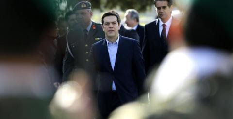 Greek Prime Minister Alexis Tsipras reviews an honor guard during his visit the Cyprus military cemetery on the outskirts of the capital Nicosia, Tuesday, Feb. 3, 2015. AP