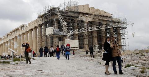 Unos turistas se hacen un selfie con el Partenon al fondo en la Acrópolis de Atenas. REUTERS/Kostas Tsironis