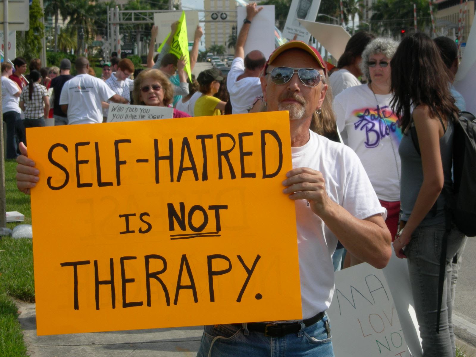 "Man in white t-shirt, jeans and red cap holds a sign that reads ""Self-Hatred is Not Therapy."""