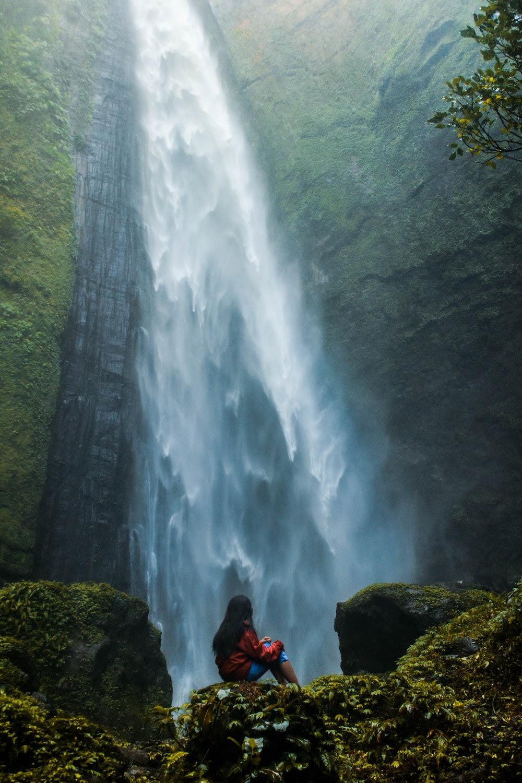 woman sitting on rock facing plunge waterfalls