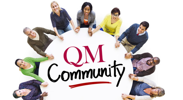 people with joined hands sitting around a table that has QM community written on it