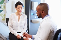 Image of a doctor completing a health assessment with a patient.
