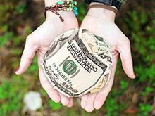 Hands holding a ball of cash