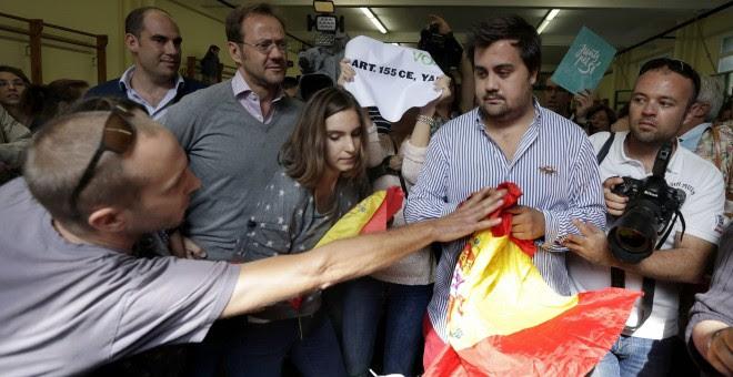 Un a persona trata de arrebatar una bandera a un miembro de VOX en el colegio donde acudió a votar en las elecciones que se celebran en Catalunya, el presidente de la Generalitat y número cuatro en las listas de Junt pel Si, Artur Mas, EFE/Alberto Estévez