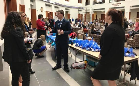 High school students congregate in the lobby of the University of Wyoming Business building dressed in professional attire during a break of their state conference for Future Business Leaders of America.