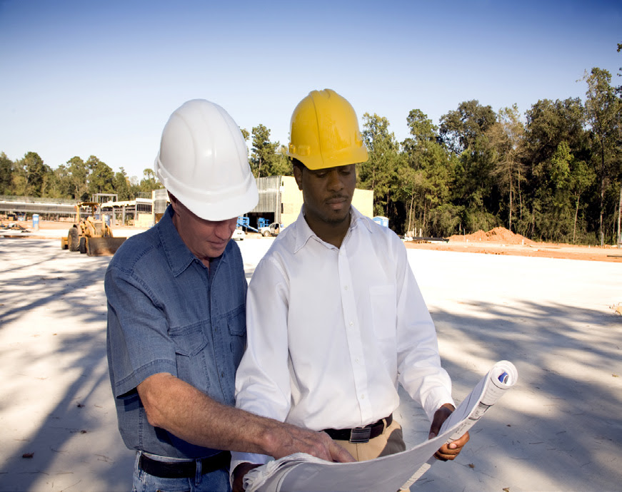 Two men in hard hats look over plans at a construction site.