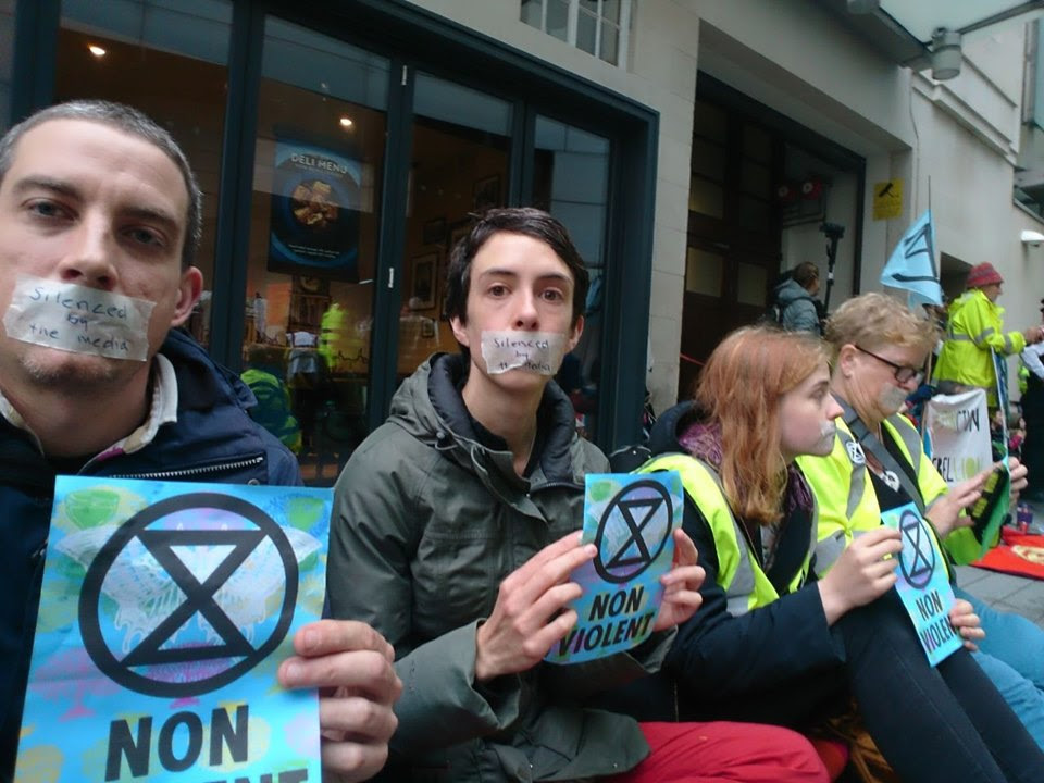 4 rebels sat outside the BBC building. They are all holding blue leaflets which have an extinction symbol on them and the text 'NON-VIOLENT'. They also have tape over their mouths with the words 'silenced by the media' written on.