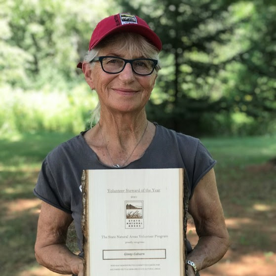 Ginny Coburn, with light skin tone, gray hair, a red baseball cap and glasses, smiles holding up her Volunteer Steward of the Year award plaque.