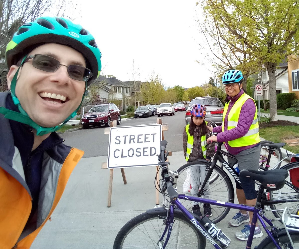 A family with helmets smiles at the camera standing on a Stay Healthy Street next to bikes and an A-frame sign that says
