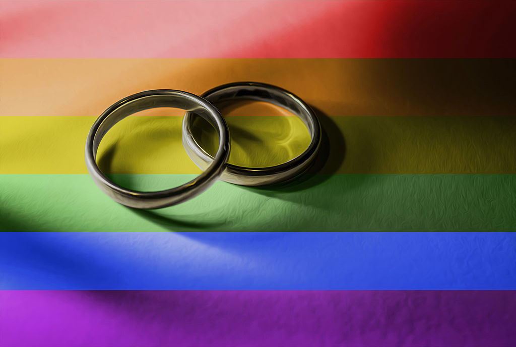 Rainbow flag with two plain wedding rings, one resting on the other