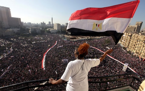 A woman waves an Egyptian national flag from a balcony overlooking Tahrir Square, Cairo on Feb 18, 2011