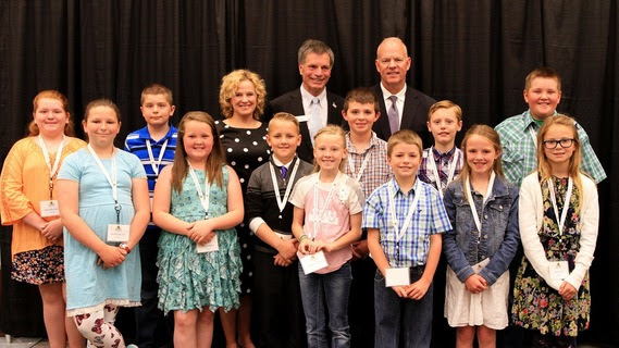 State Superintendent Jillian Balow, State Treasurer Mark Gordon, and Wyoming Governor Matt Mead stand with the twelve elementary school bookmark winners.