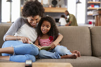African American Mother and Daughter Reading on the Couch