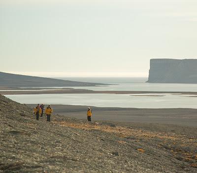 Passengers walk across the Arctic tundra