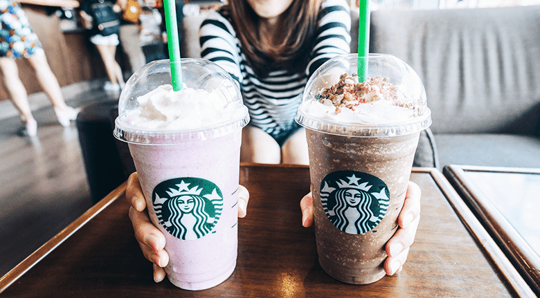 Woman holds a chocolate Frappuccino in one hand, and a strawberry Frappuccino in the other