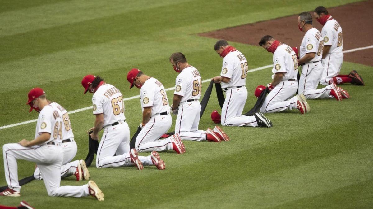 Baseball players taking a knee.