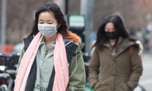 Pedestrians wear face masks as they walk in downtown Toronto Monday.