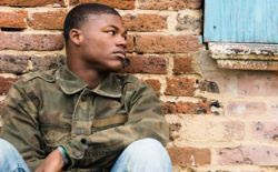 image of a homeless youth sitting against a brick wall